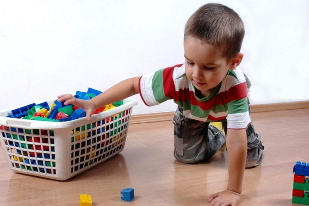 ребенок убирает свои игрушки